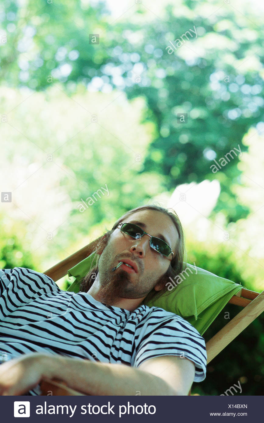 Man wearing sunglasses reclining in chair, smoking hand-rolled cigarette - Stock Image