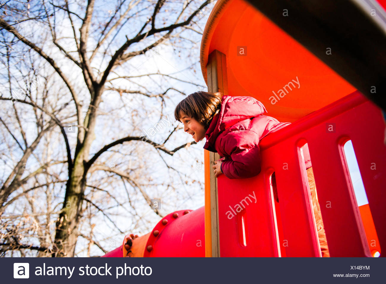 Boy looking out from top of red playground slide Stock Photo