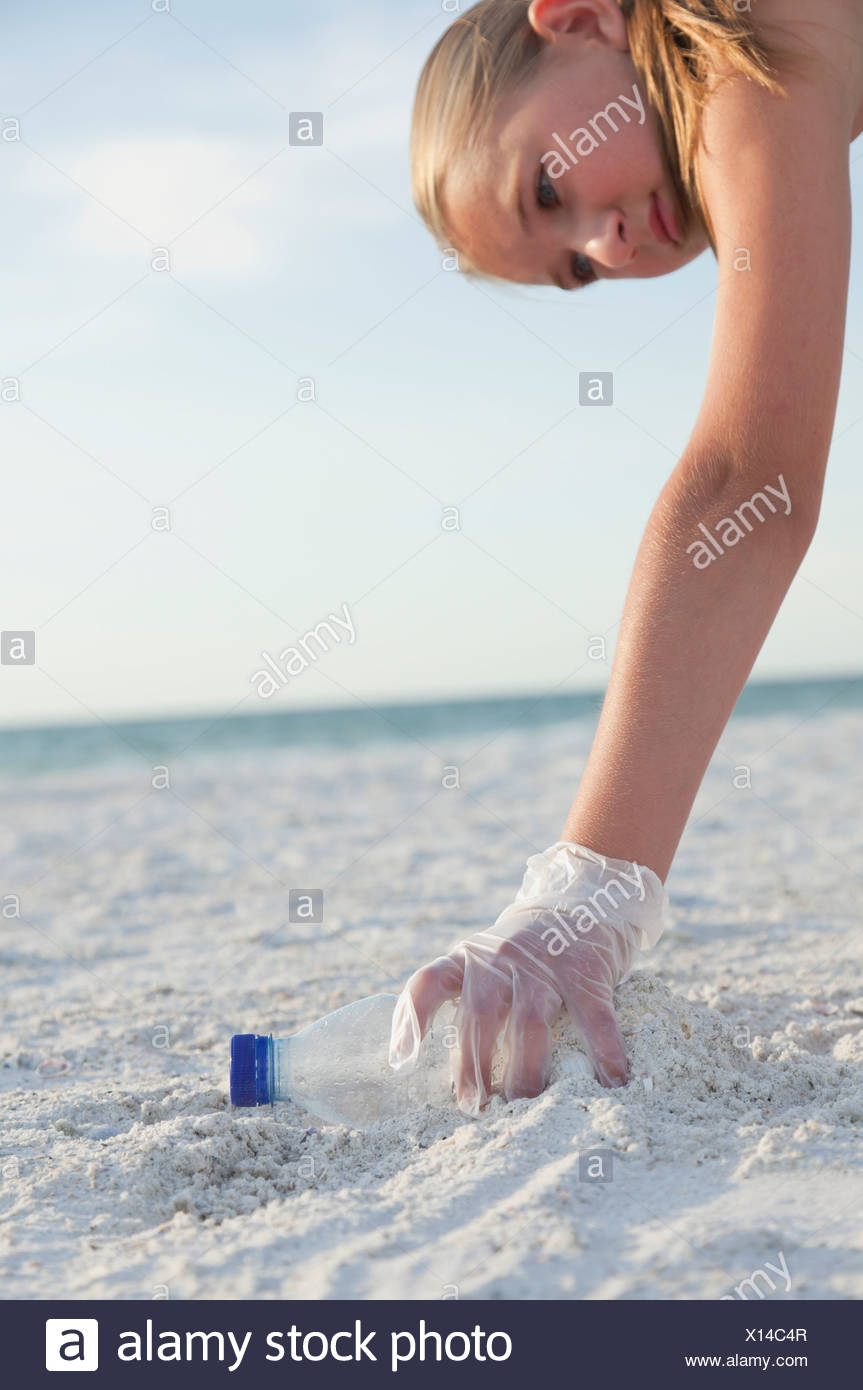 USA, Florida, St. Petersburg, Cose-up of girl (10-11) cleaning beach, reaching for plastic bottle - Stock Image
