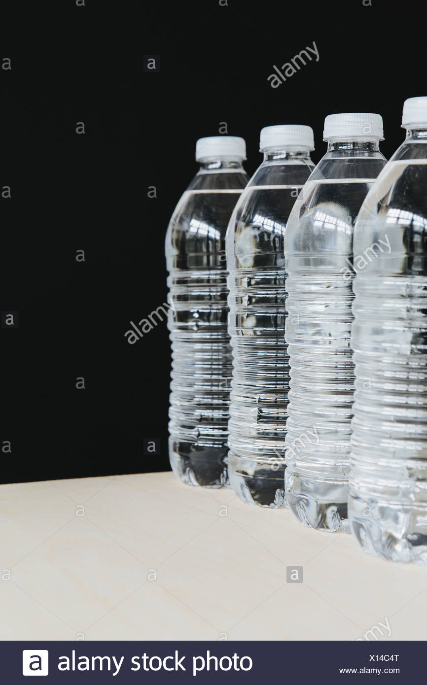 Row of clear, plastic water bottles filled with filtered water in a row. on a black background. - Stock Image