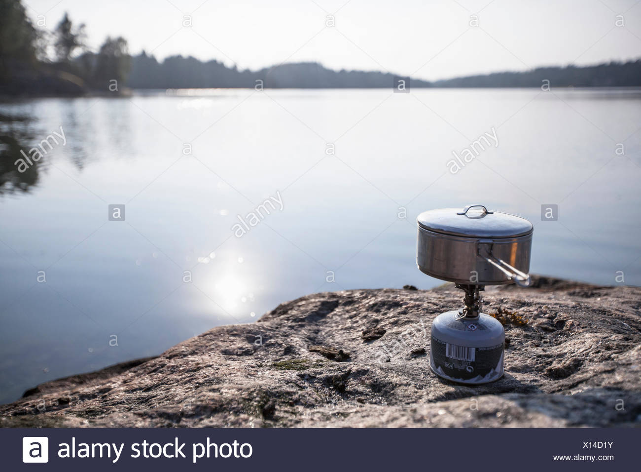 Cooking utensil on camping stove at lakeshore - Stock Image