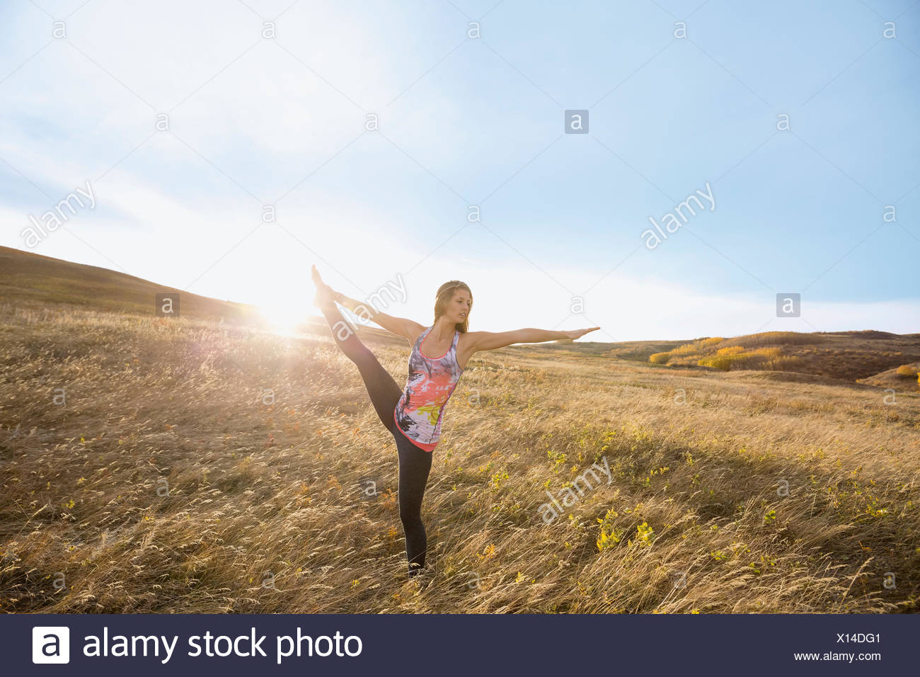 Woman practicing yoga in sunny rural field - Stock Image