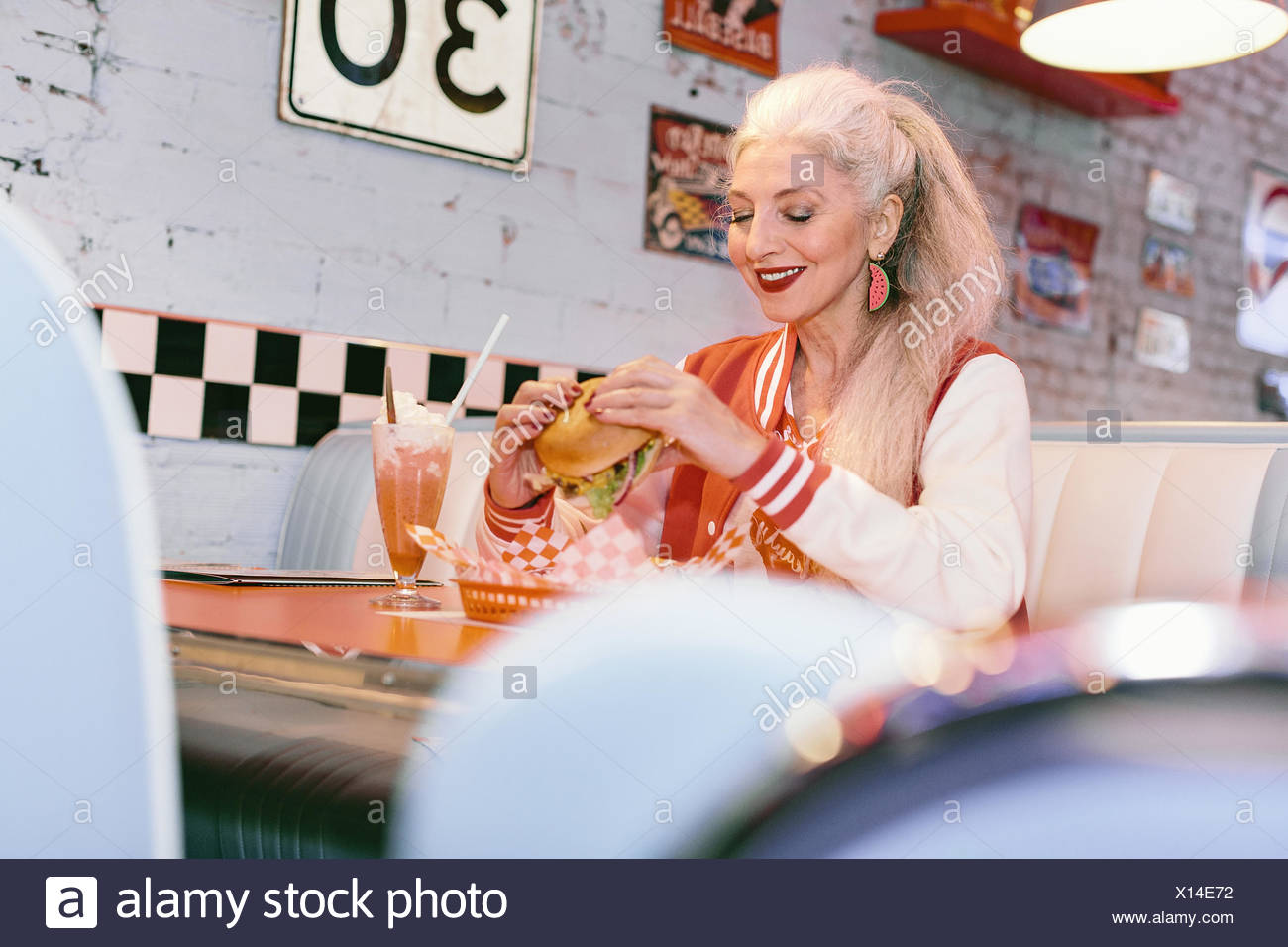 Mature woman in baseball jacket eating burger in 1950's diner - Stock Image