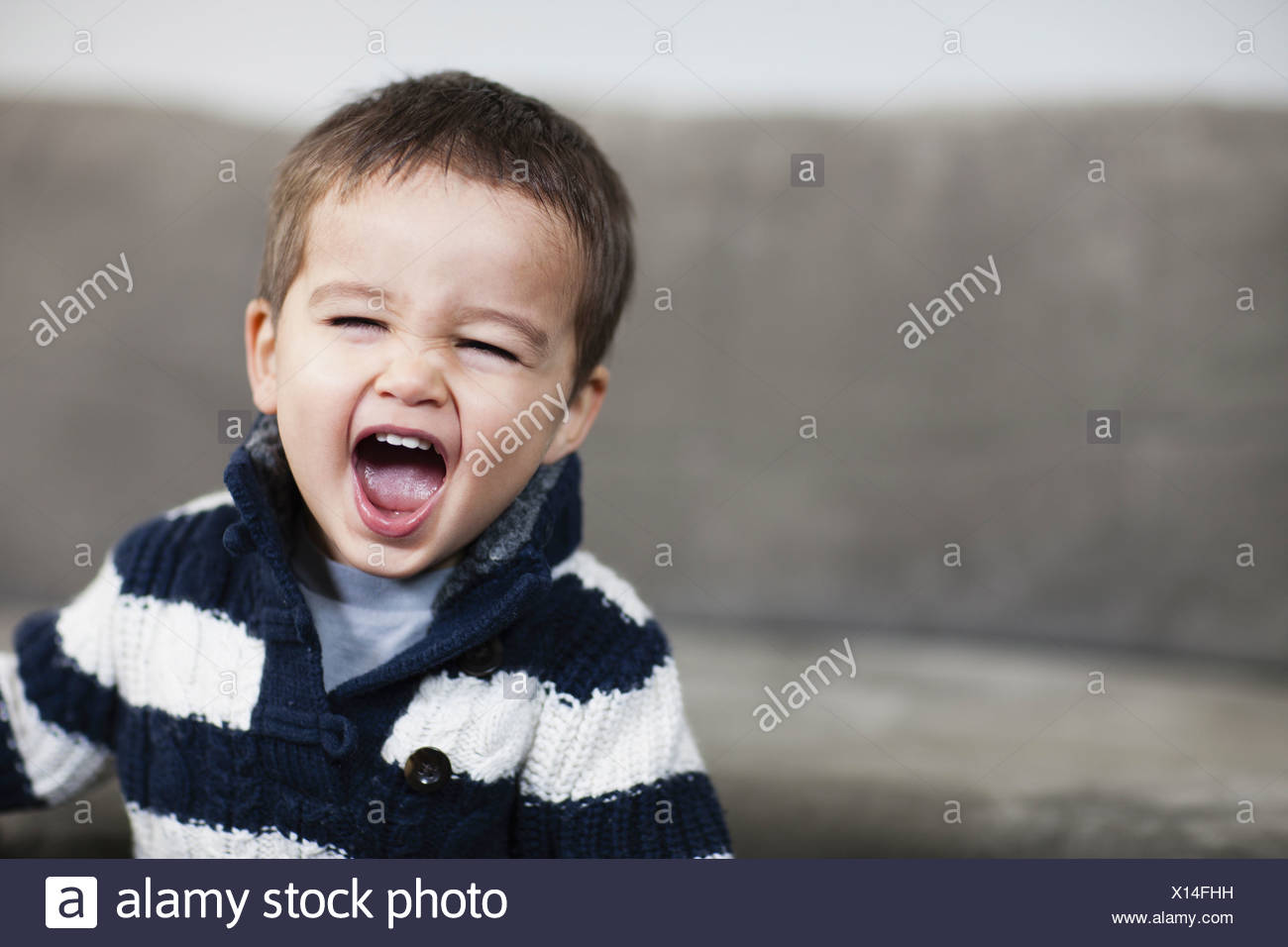 A boy in a striped shirt opening his mouth wide  Pennsylvania USA - Stock Image