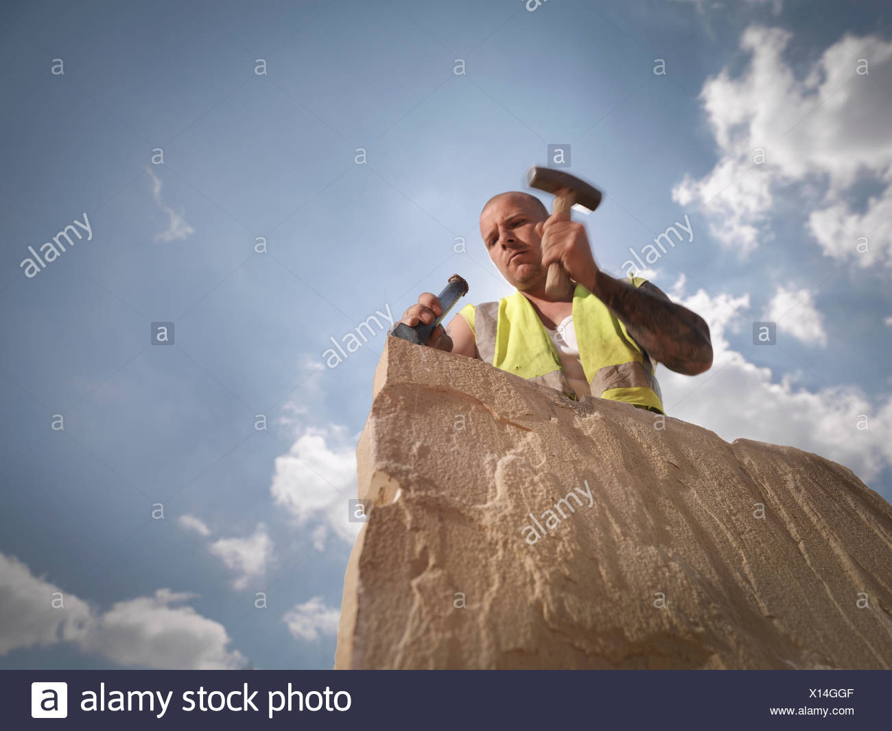 Quarry worker splitting sandstone in Yorkshire stone quarry - Stock Image