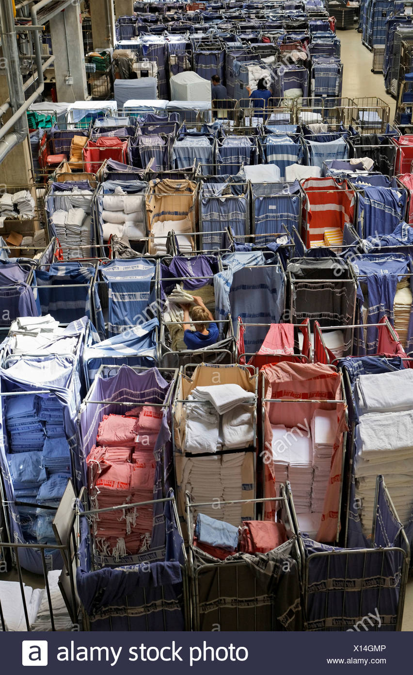 Freshly laundered rental linen sorted in trolleys and waiting in a room to be pressed Stock Photo