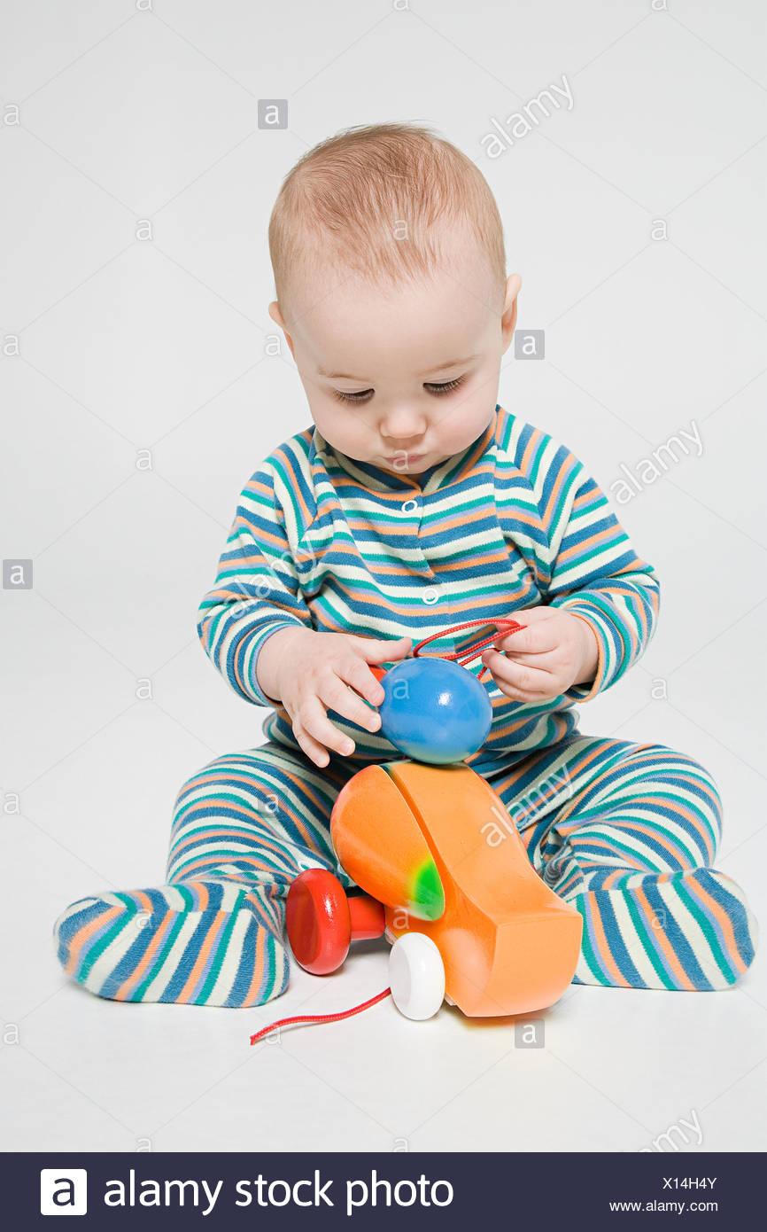 A baby boy playing with a toy duck - Stock Image