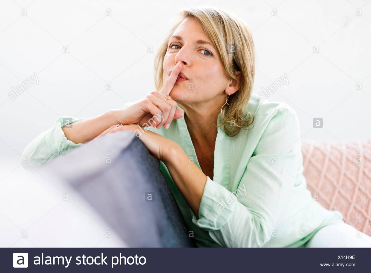 Portrait of woman sitting on sofa with finger on lips - Stock Image