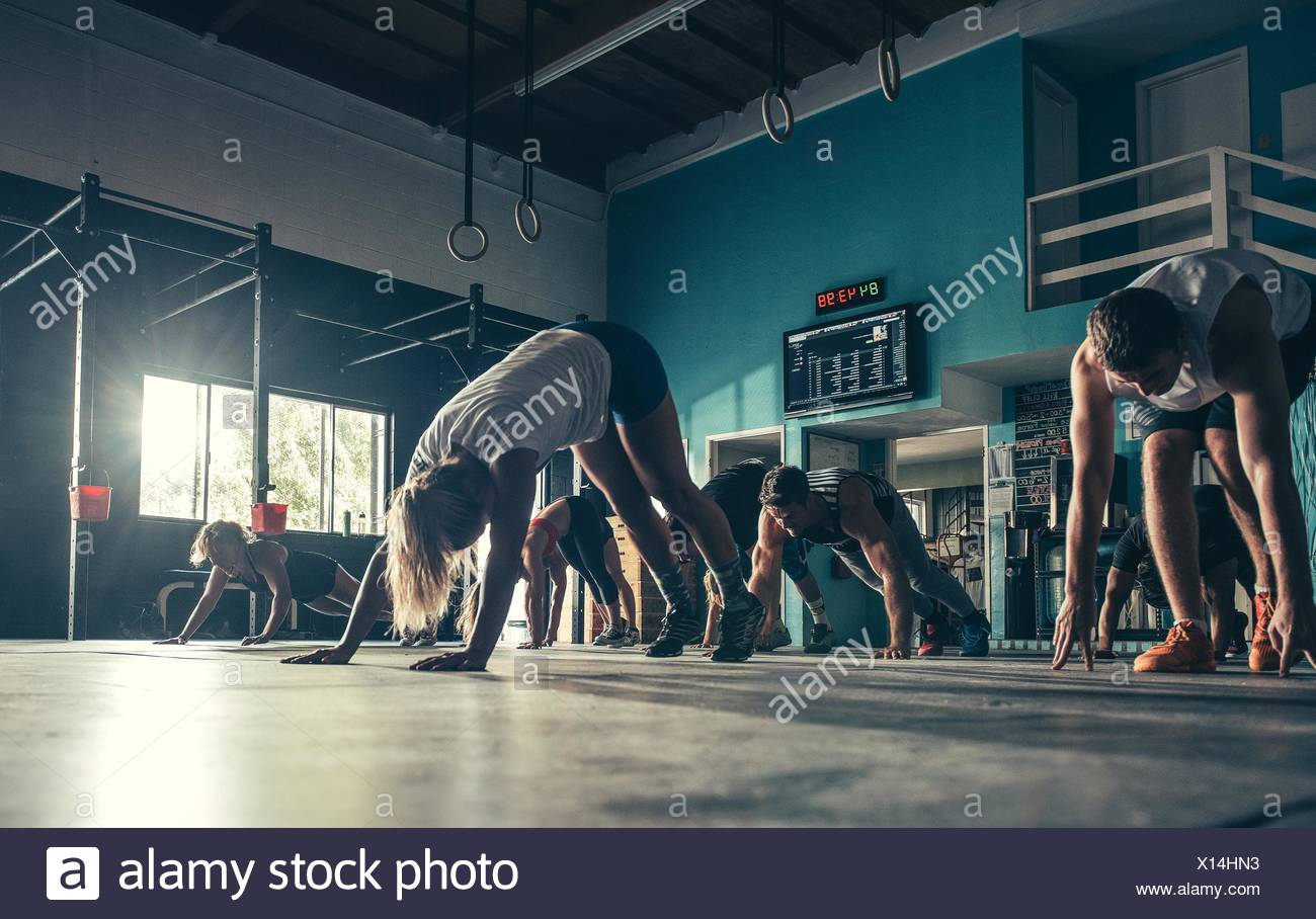 Surface level view of people exercising together in gym - Stock Image