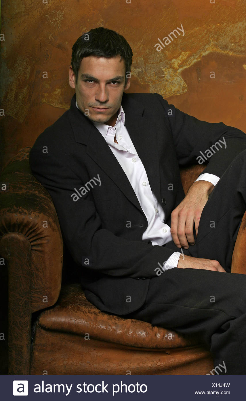 Young man sitting on chair, portrait - Stock Image