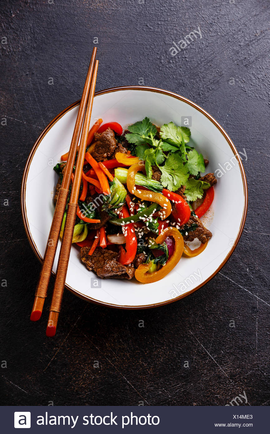 Szechuan beef stir fry with vegetables in bowl on dark background Stock Photo