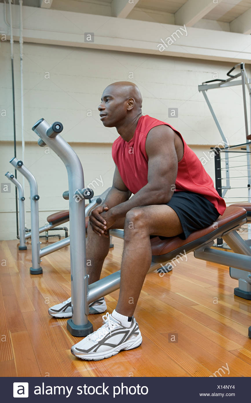 A man taking a break from weightlifting - Stock Image
