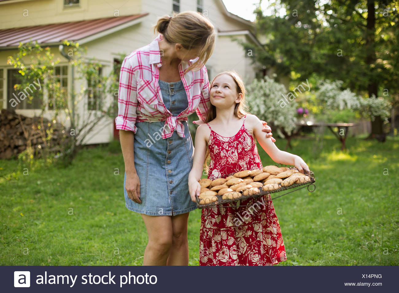 Baking homemade cookies. A young girl holding a tray of fresh baked cookies, and an adult woman leaning down to praise her. - Stock Image