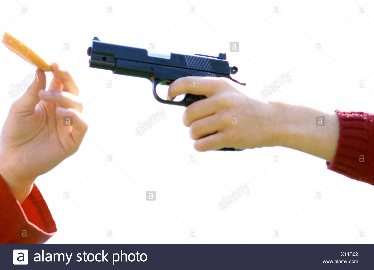 Children's hands, one holding gun, the other holding slice of fruit - Stock Image