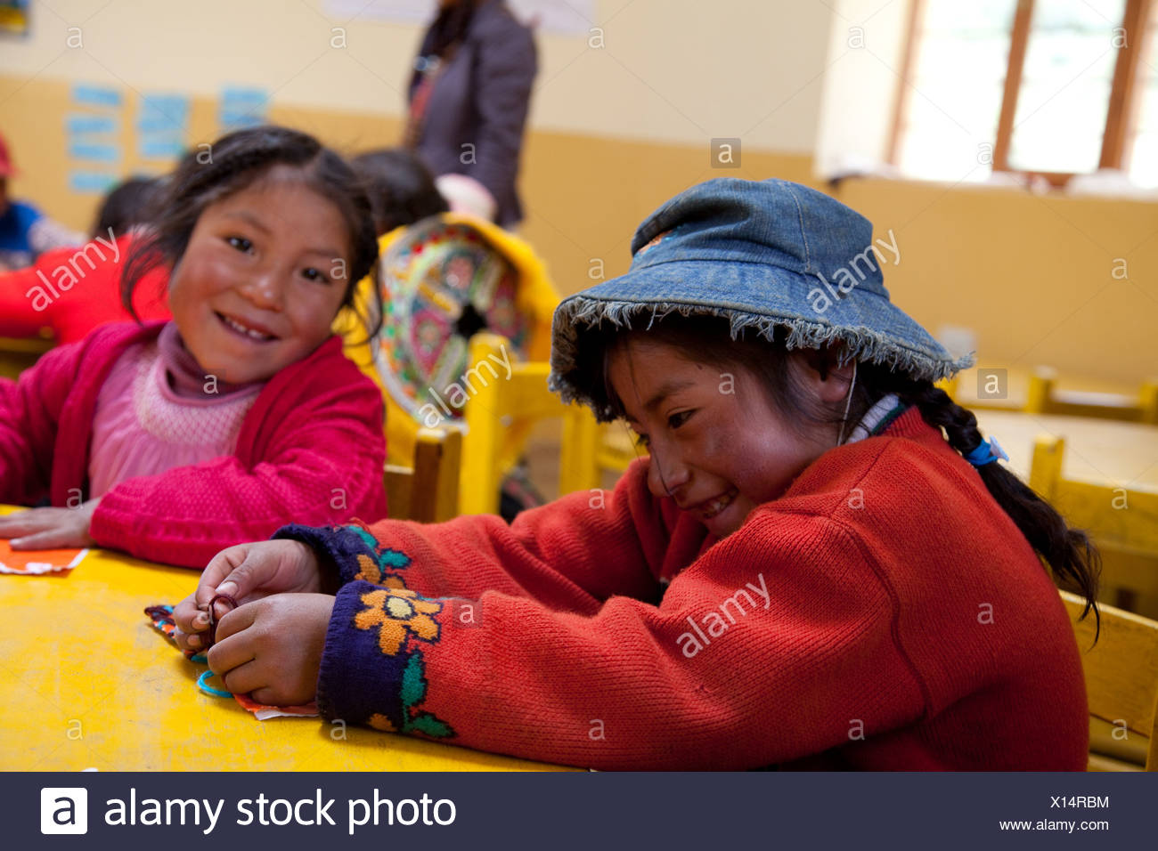 Two girls giggle at a preschool near Qusicancha, Peru. - Stock Image