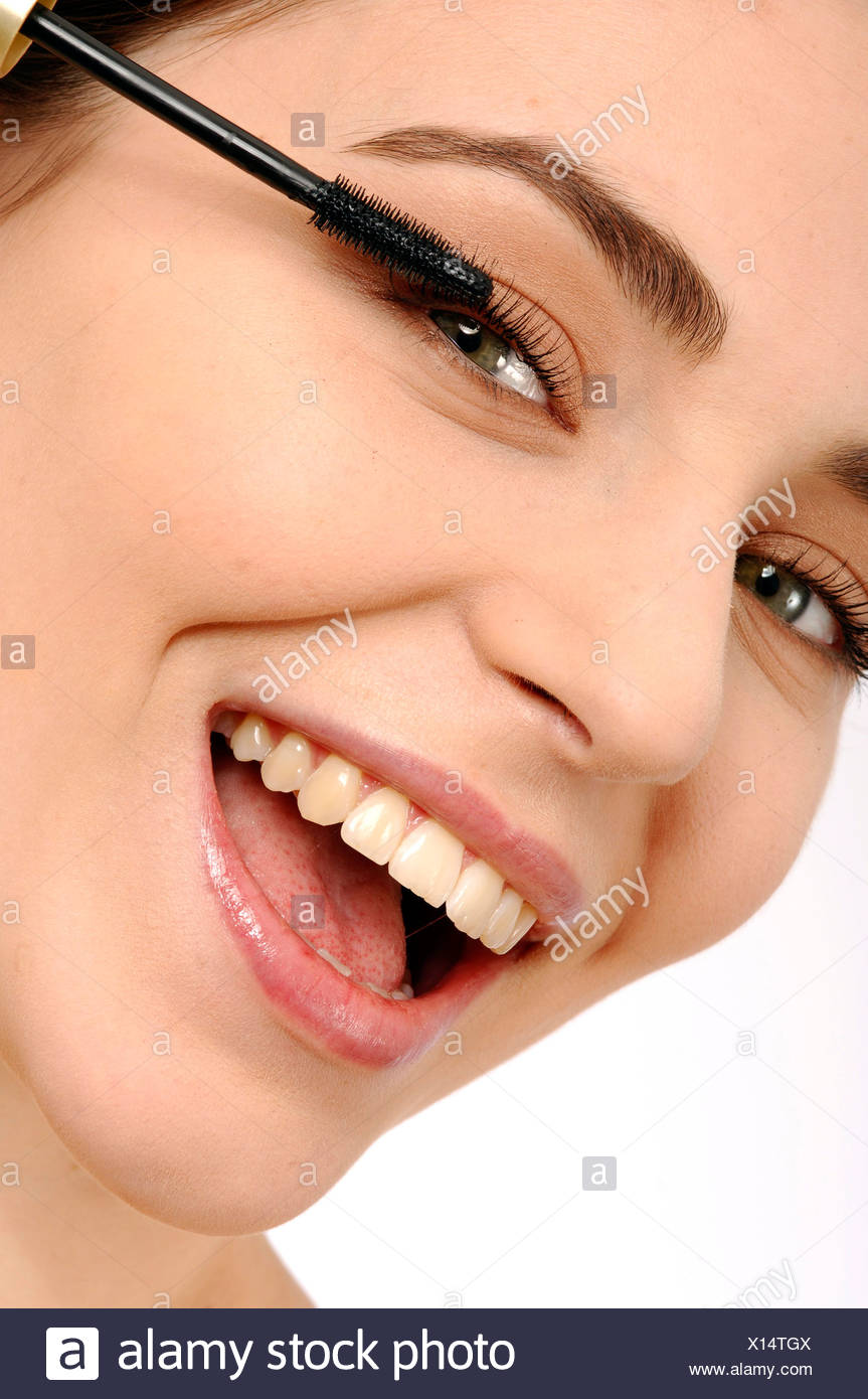 0178e4f76c9 Female brunette hair off face applying mascara to top eyelashes looking  sideways to camera mouth open smiling showing teeth