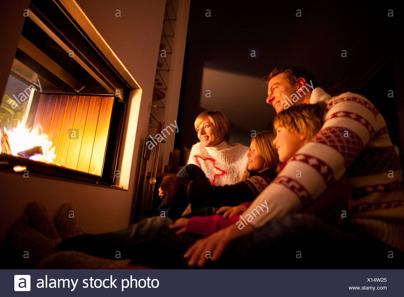 Mid adult family sitting together near fireplace - Stock Image