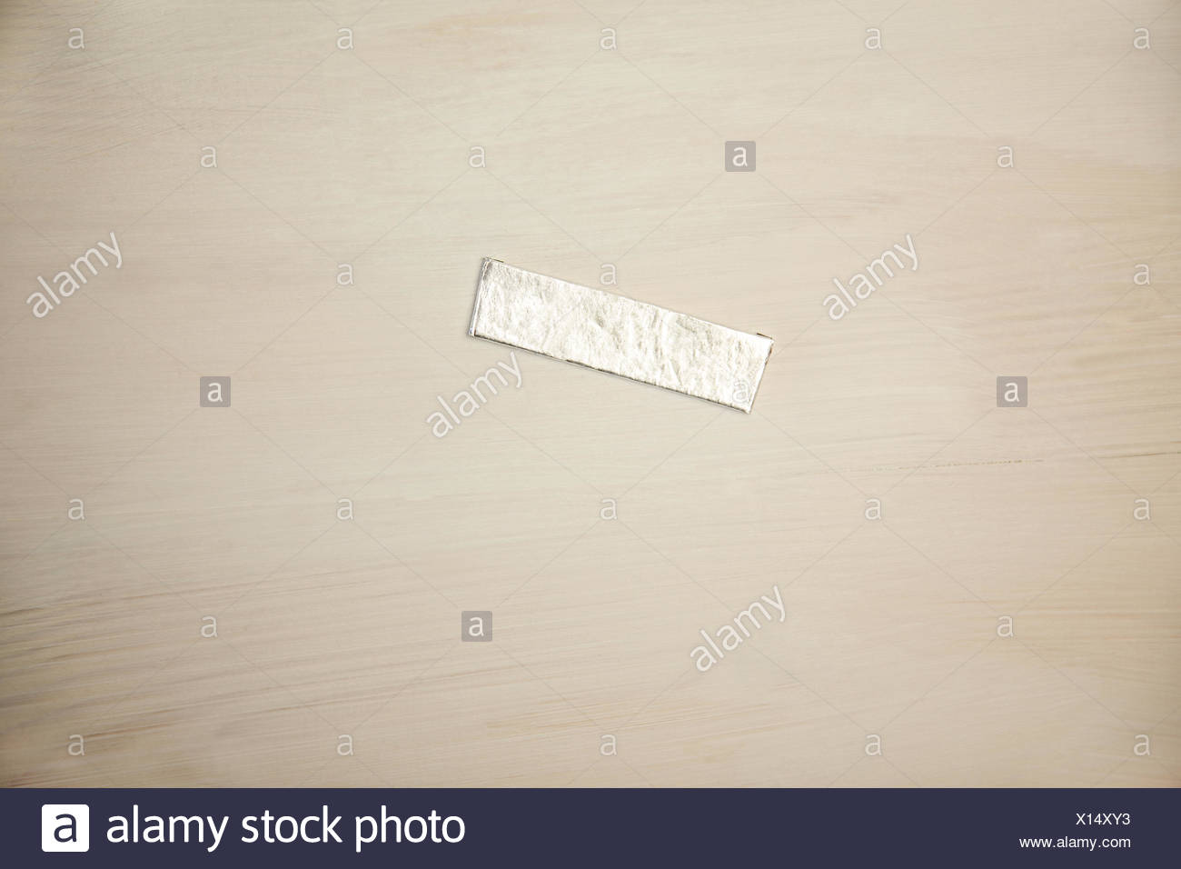 Chewing gum wrapper on wooden desk - Stock Image