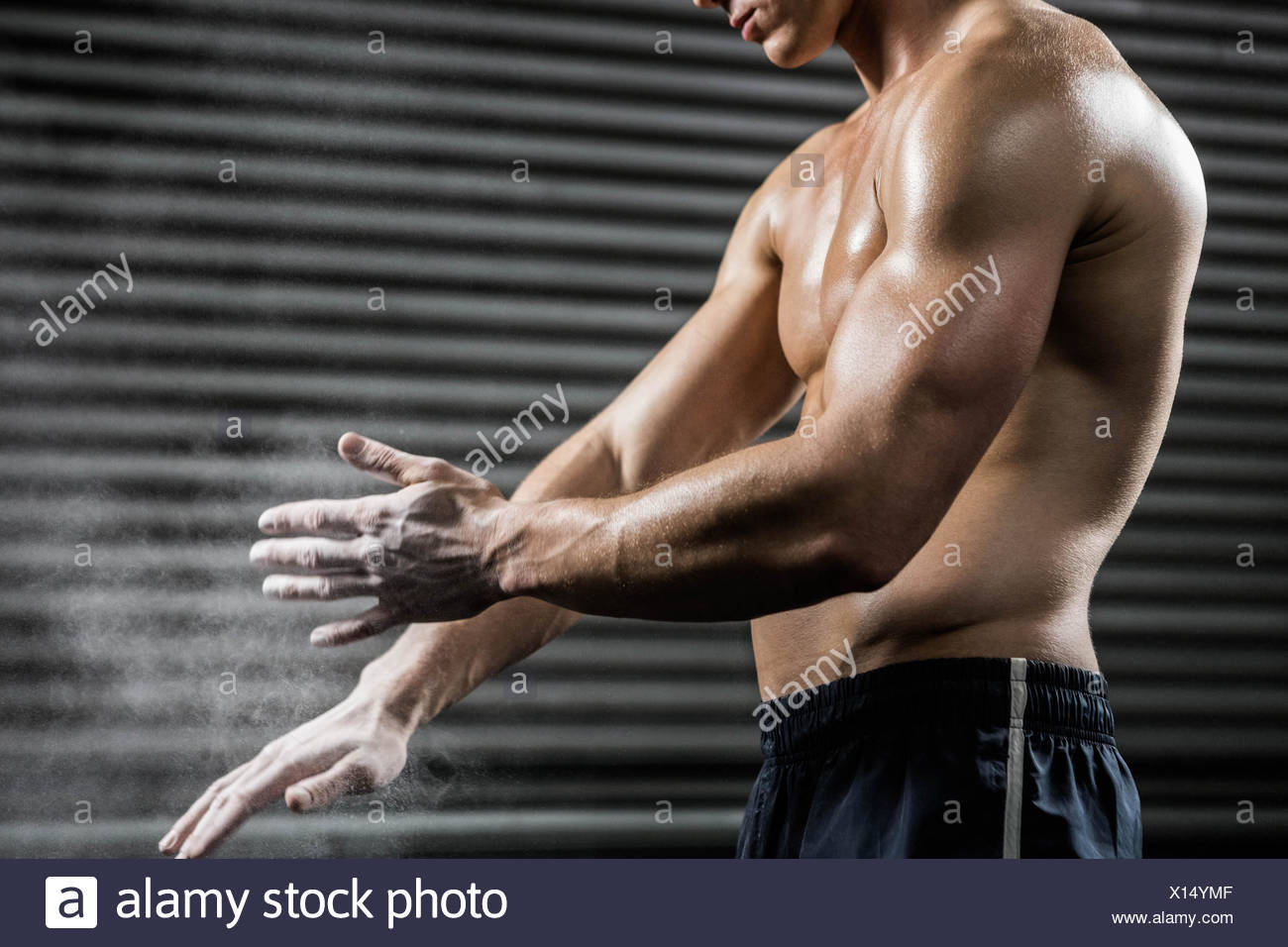 Shirtless man clapping hands with talc - Stock Image