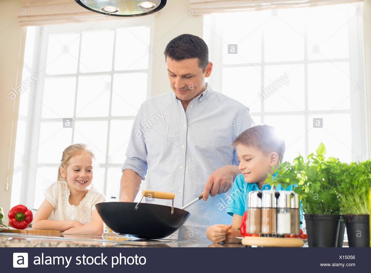 Children looking at father preparing food in kitchen - Stock Image
