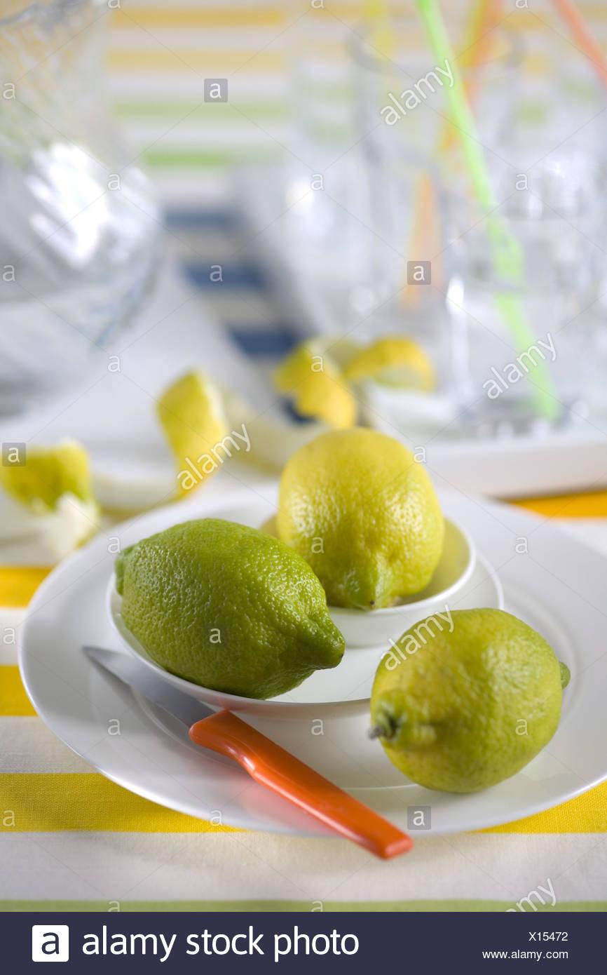 Three lemons on white plates, - Stock Image