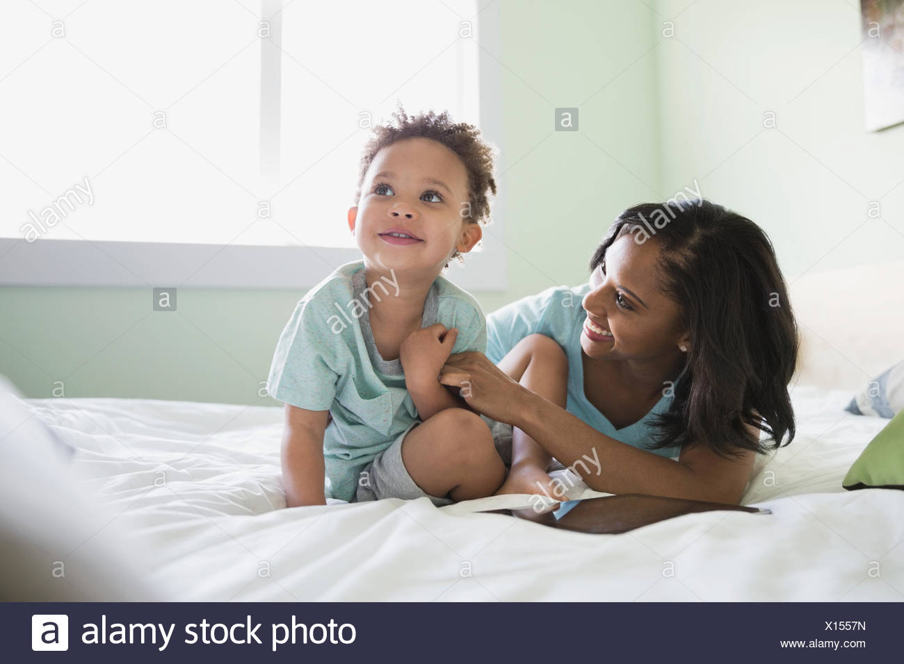 Playful mother with baby on bed at home - Stock Image