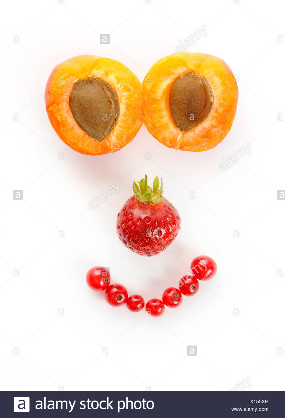 Face made of fruit, Apricots (Prunus armeniaca), Strawberries (Fragaria), Currants (Ribes) Stock Photo