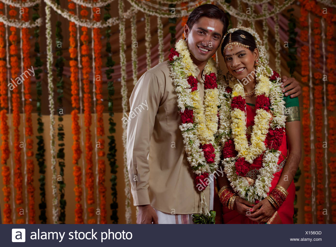 fc1375b62f Portrait of young bride and groom wearing garlands during traditional Indian  wedding