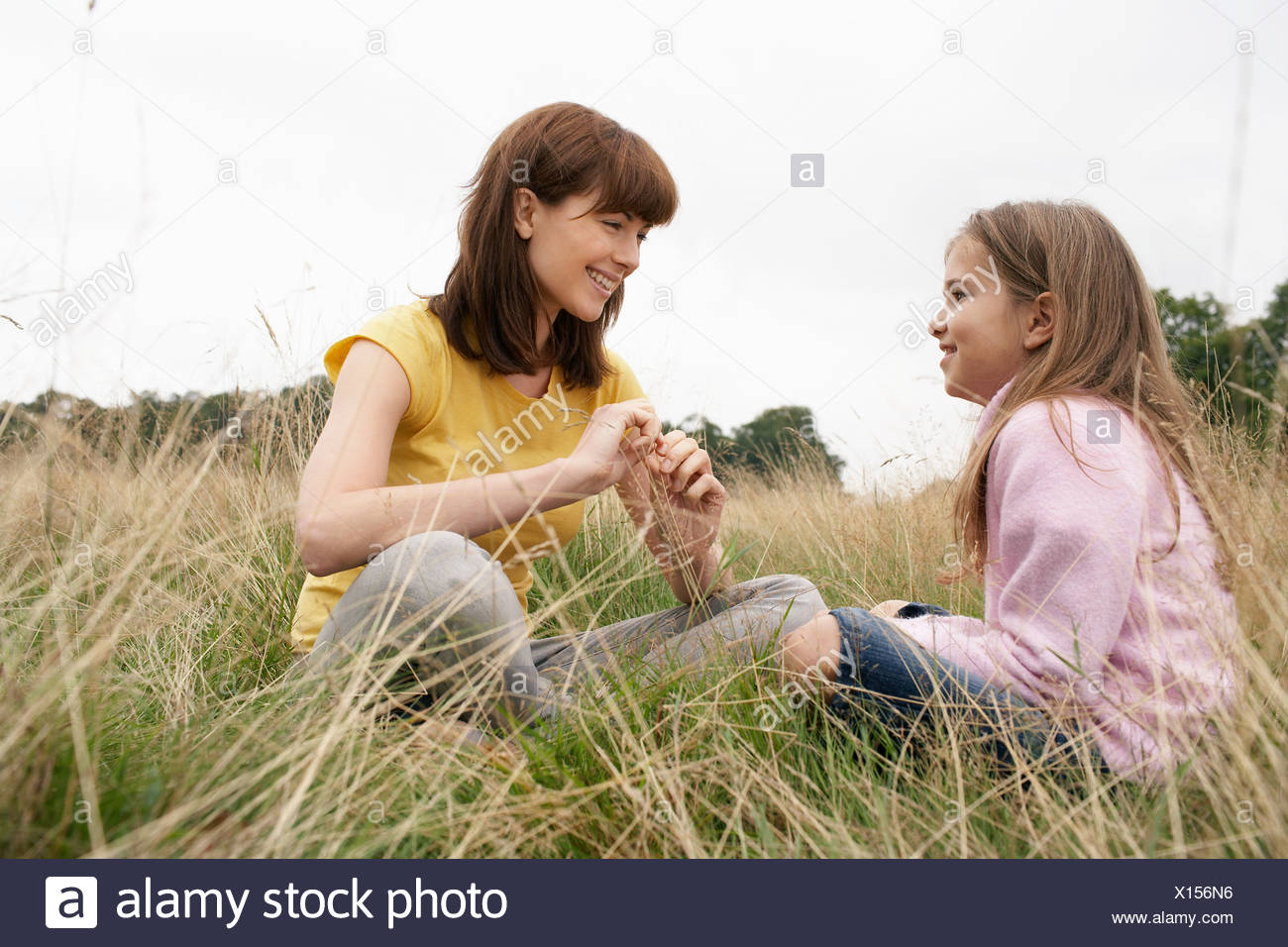 Mother and daughter sitting in a field - Stock Image