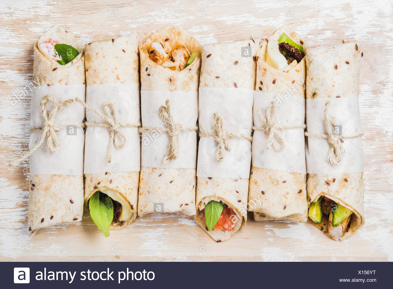 Tortilla wraps with various fillings on shabby white painted wooden background, top view, horizontal composition. Healthy snack - Stock Image