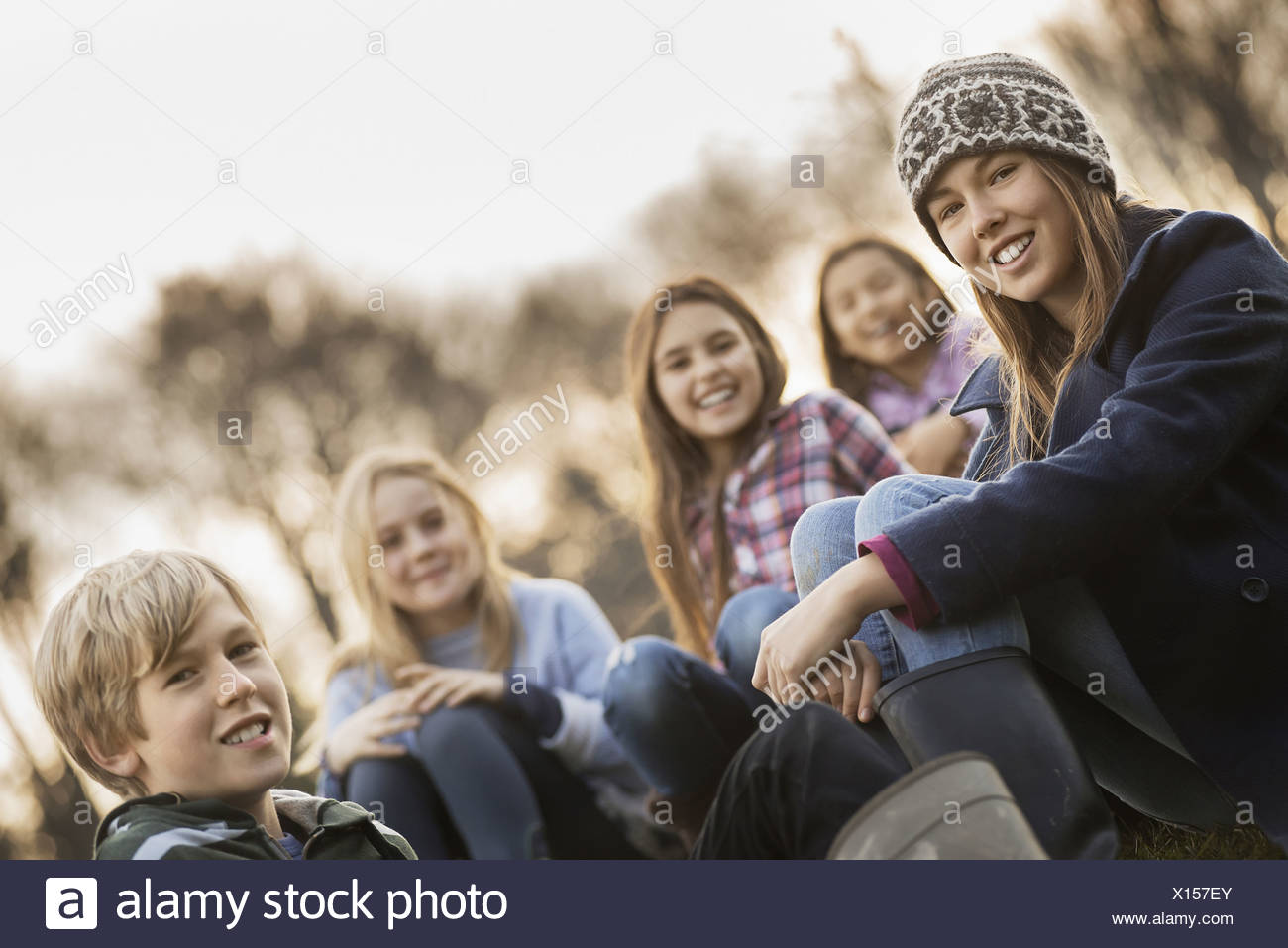 Five children on a farm Boys and girls in warm jackets outdoors - Stock Image
