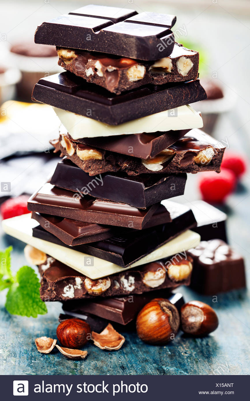 An assortment of  white, dark, and milk chocolate with nuts on wooden background - Stock Image