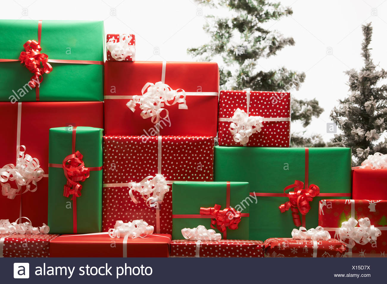 Christmas gifts by tree - Stock Image