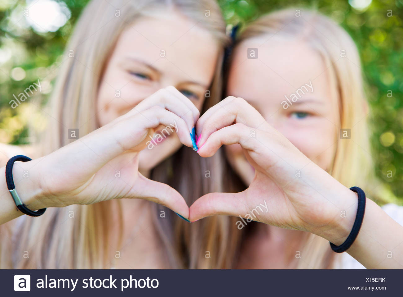 Girl friends (12-13) and heart shape gesture - Stock Image