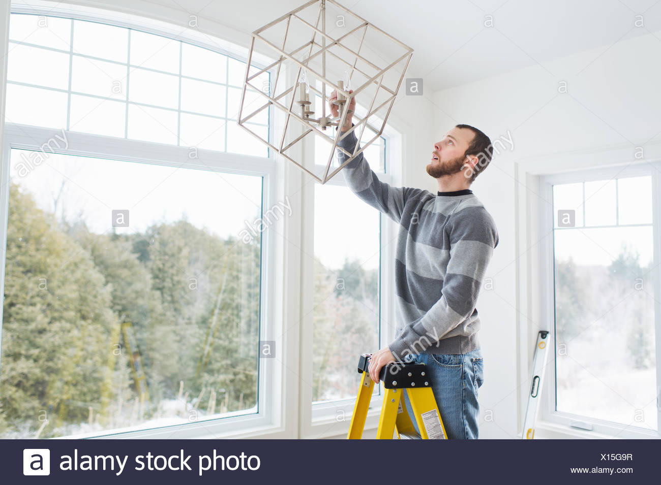 Young man installing ceiling light - Stock Image