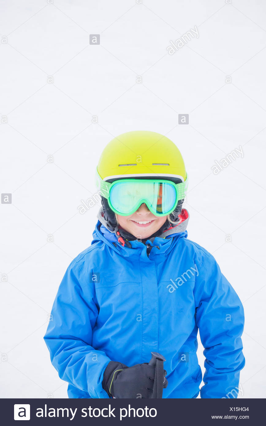 Smiling boy (10-11) wearing helmet and ski goggles against snow - Stock Image