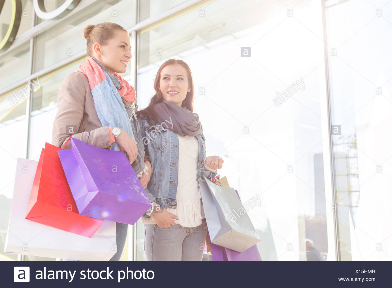Young women carrying shopping bags by store Stock Photo