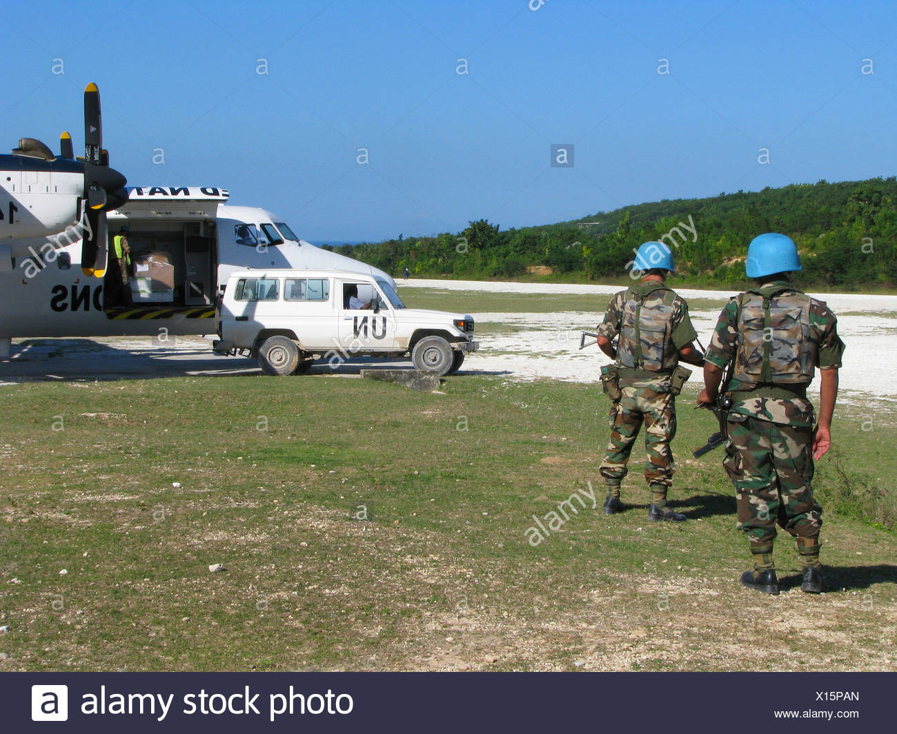 Soldiers of the 'United Nations Stabilisation Mission in Haiti' secure UN aircraft with machine gun and assault rifle next to unpaved runway, Haiti, Grande Anse, Jeremie - Stock Image