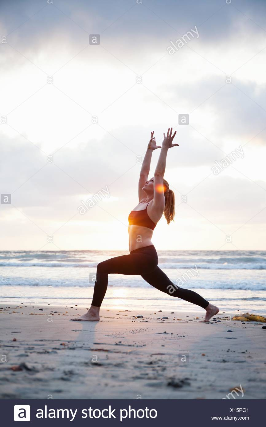 Mid adult woman practicing warrior yoga pose on beach at sunset - Stock Image