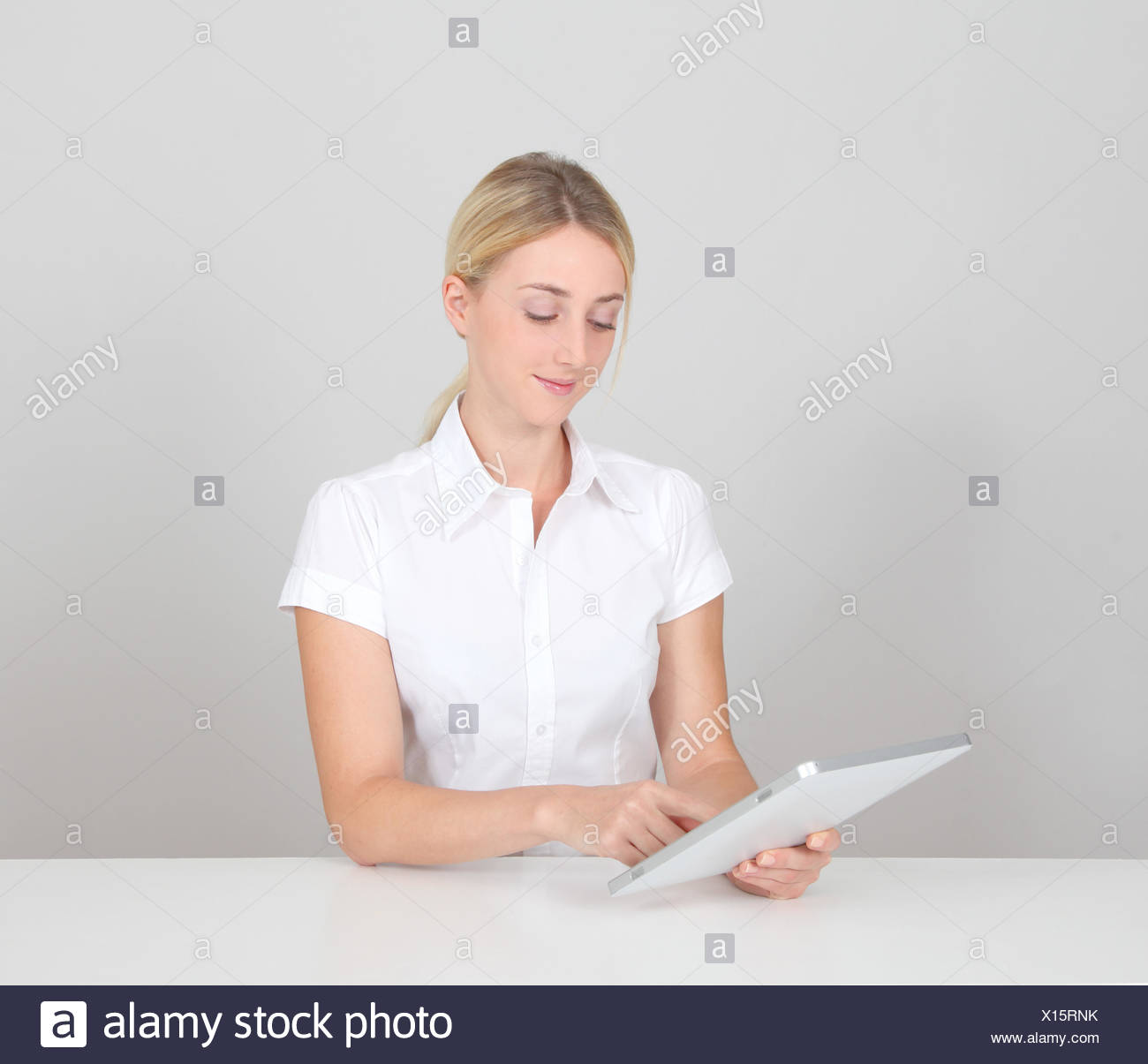 Woman on white background using electronic tablet - Stock Image