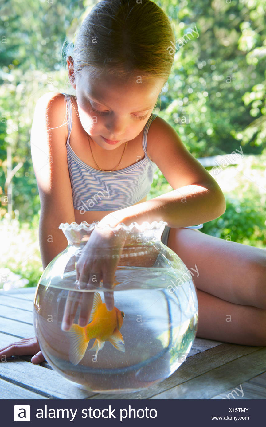 Young girl with fingers in goldfish bowl - Stock Image