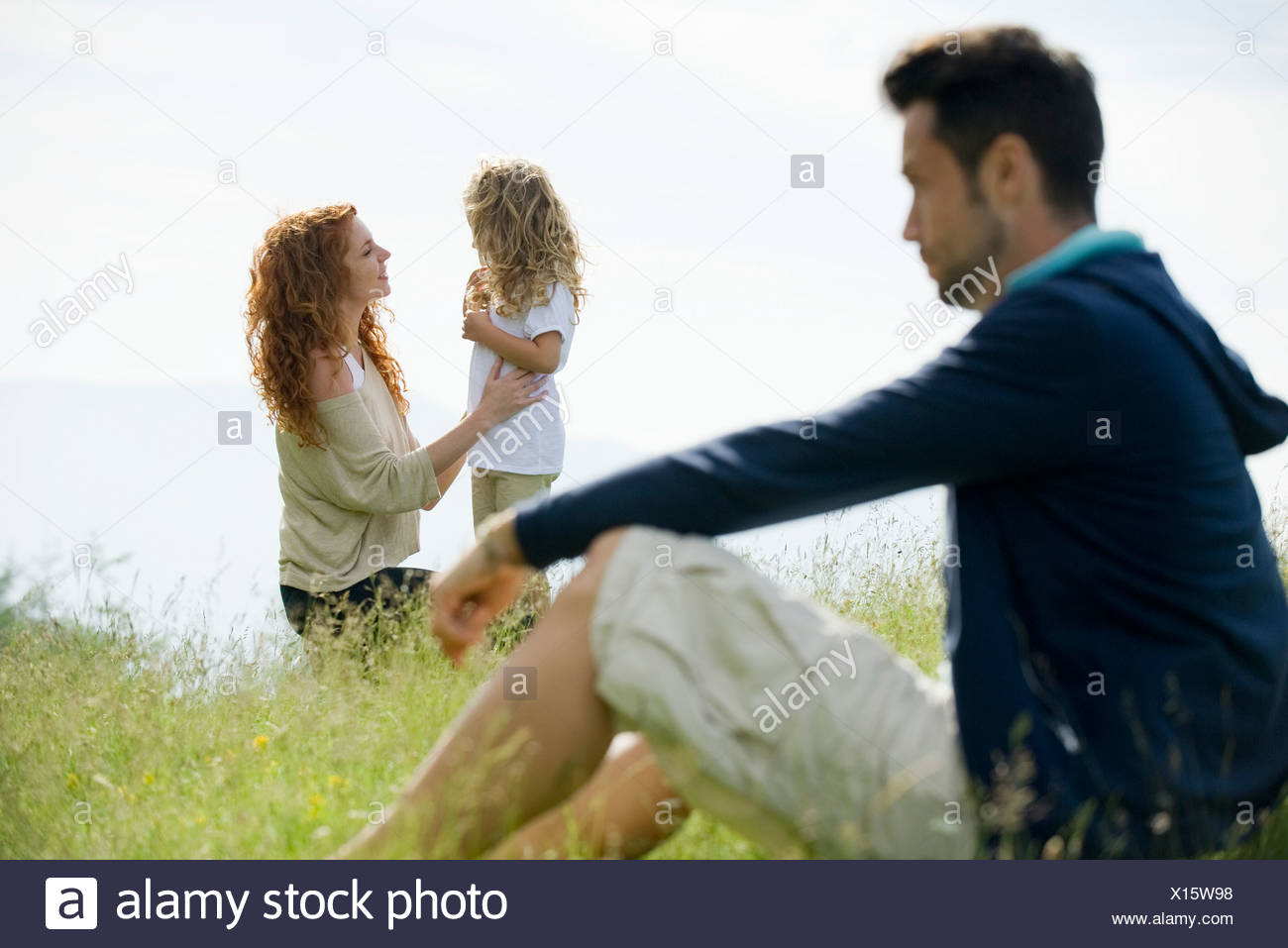 Mother talking with young daughter outdoors, father watching from foreground - Stock Image