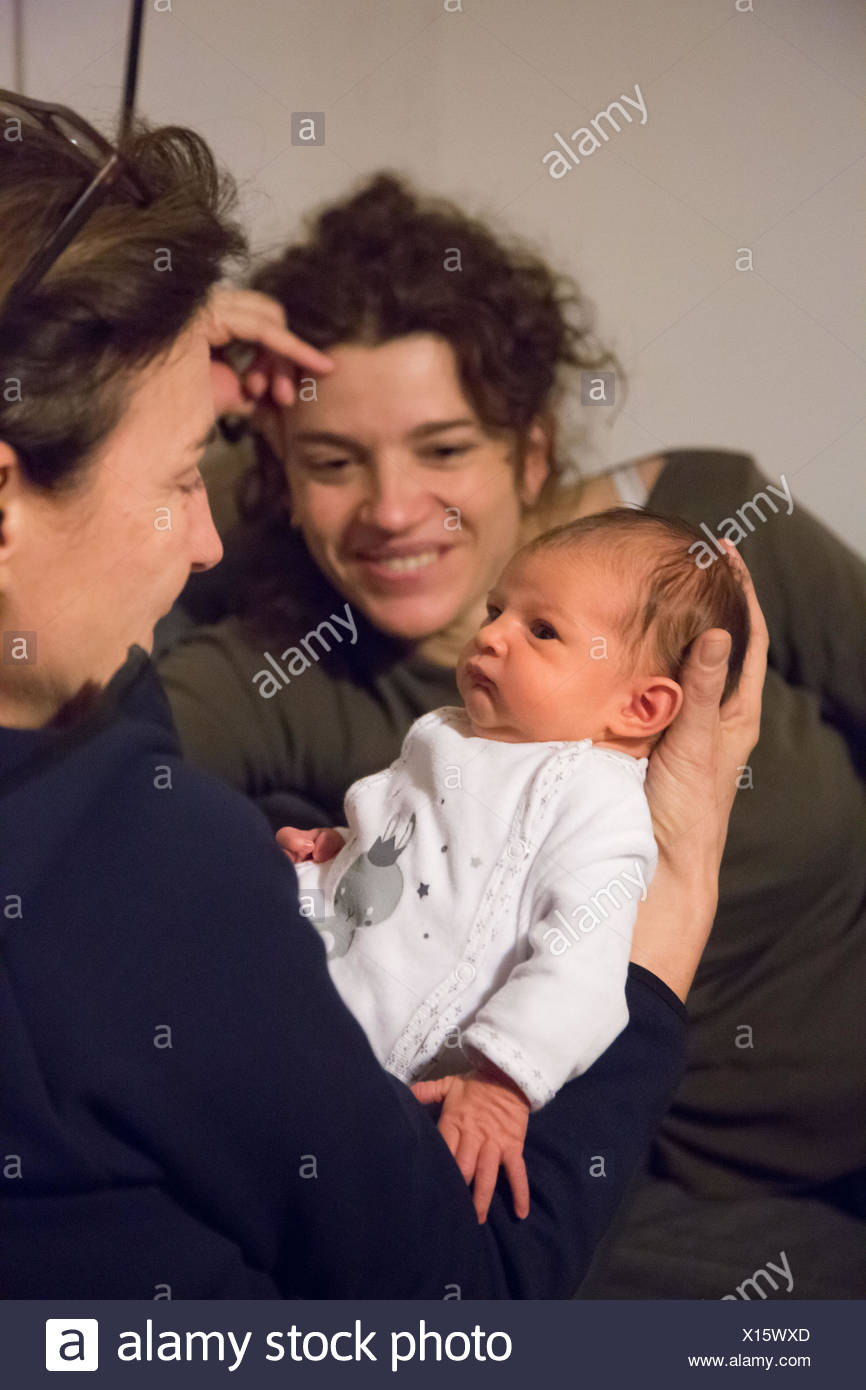 Newborn baby in the arms of a woman. - Stock Image