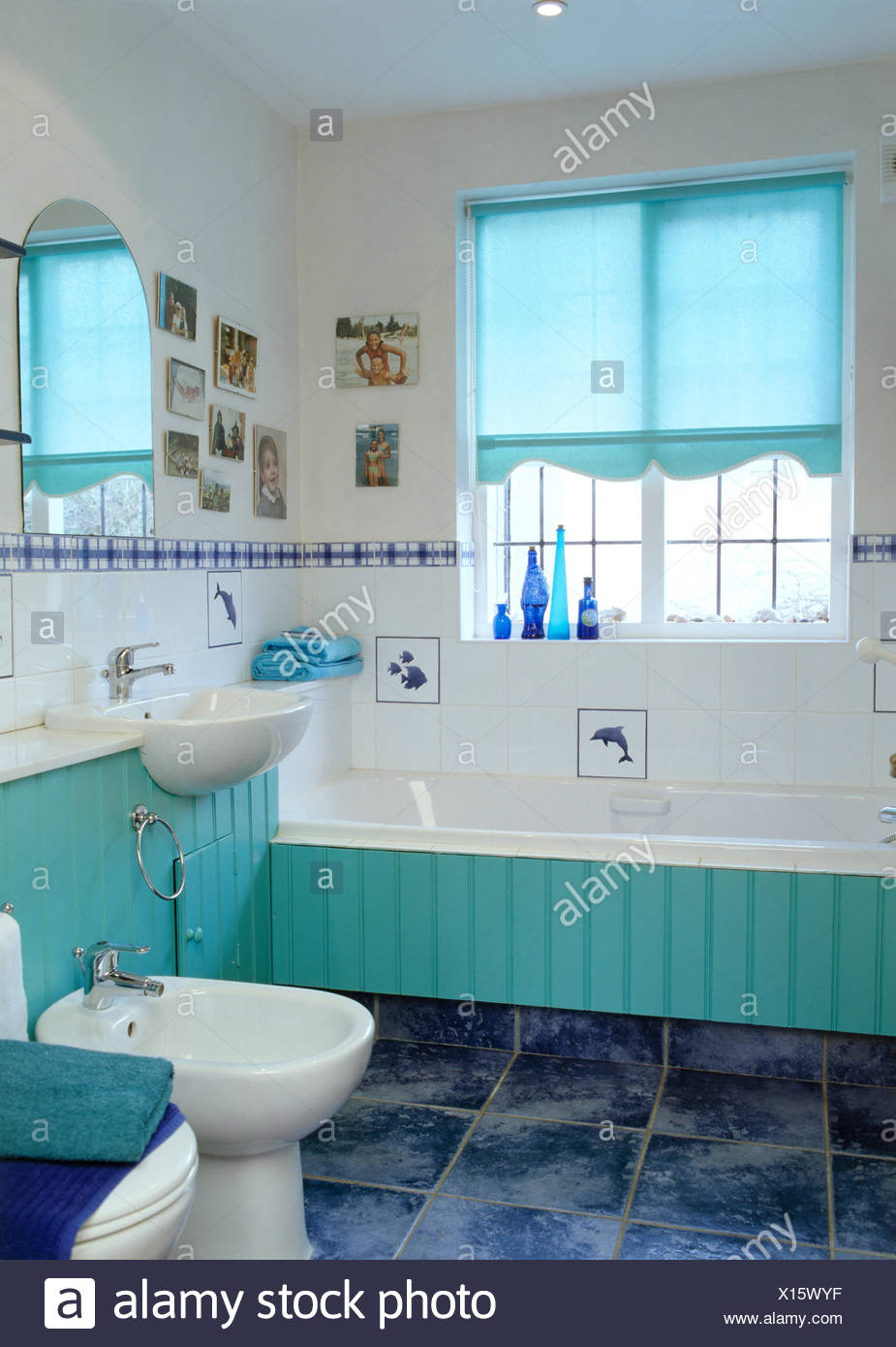 Turquoise Blind On Window Above Turquoise Tongue+groove Panelled Bath In Small  White Bathroom With White Bidet