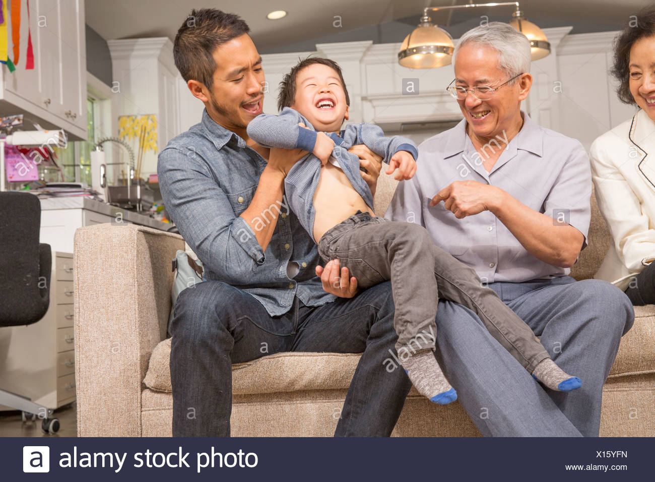 Three generation family playing with young boy on sofa - Stock Image