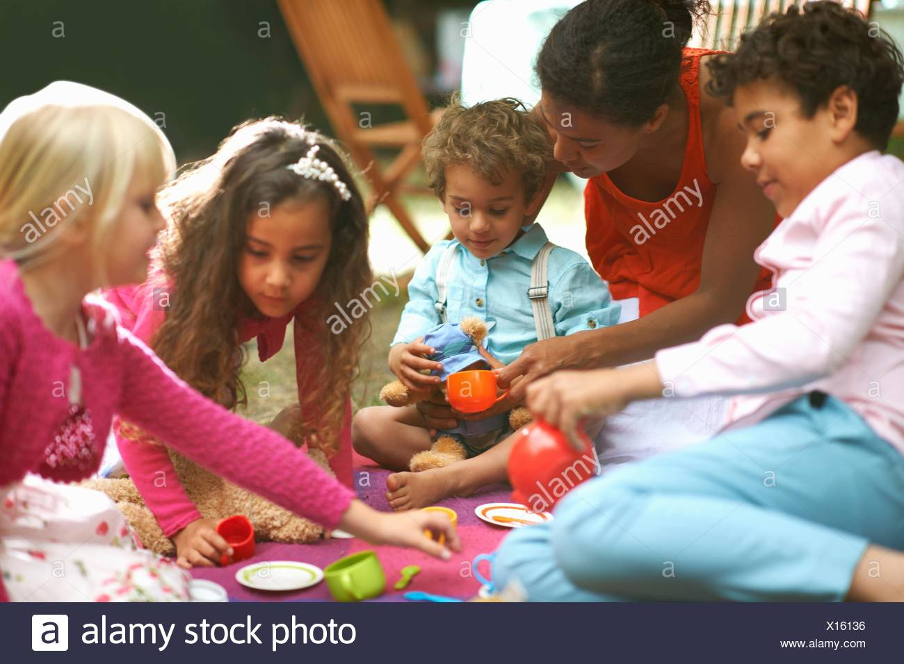 Mother and four children playing picnics at garden birthday party - Stock Image