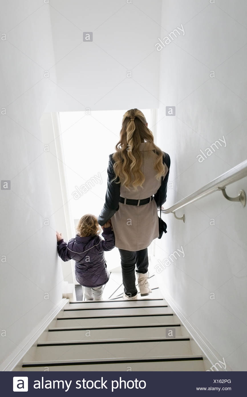 Mother and son (4-5) walking down stairs Stock Photo
