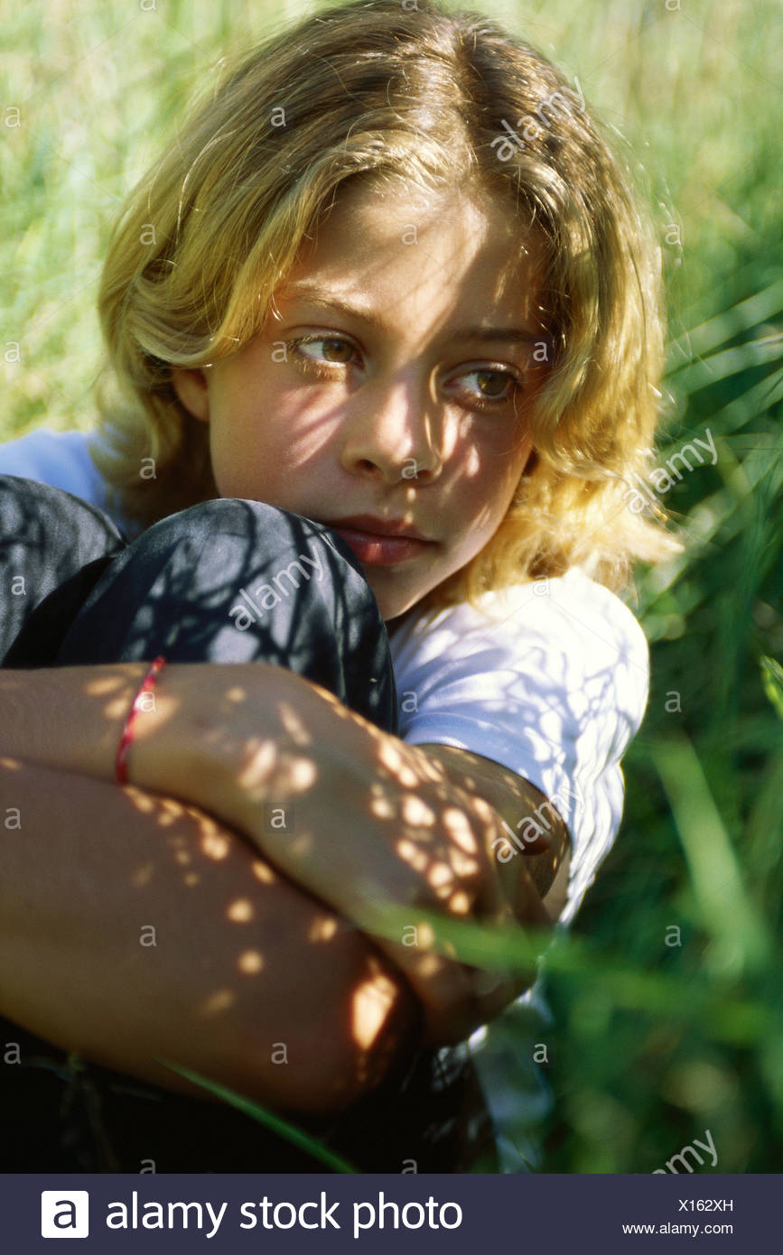 Girl sitting in shade, holding knees, close-up - Stock Image