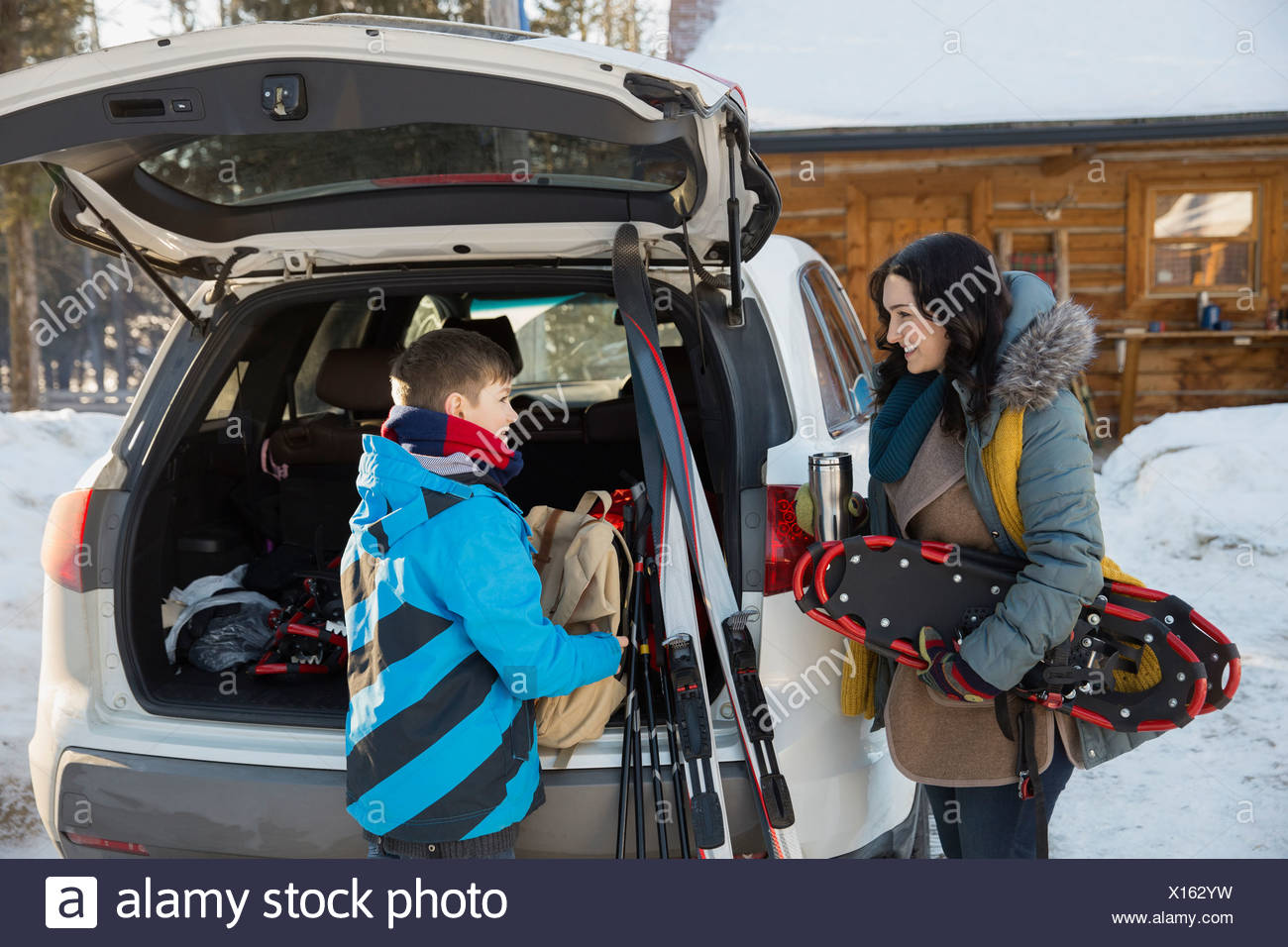 Mother and son unloading winter sports gear from car - Stock Image