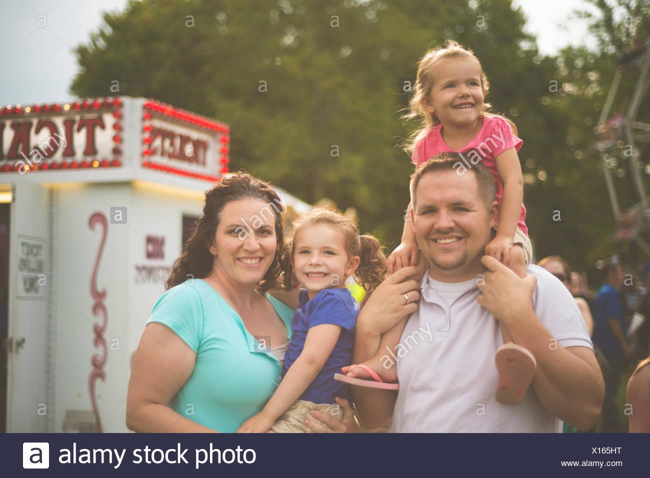 Family portrait of mid adult couple and two young daughters at funfair - Stock Image